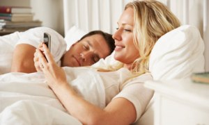 Woman Using Mobile Phone In Bed